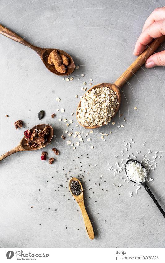 Muesli ingredients on spoons on a rustic background Cereal Ingredients Spoon Hand Breakfast Nutrition Diet Organic Oat flakes Almond sciatic seed coconut flakes