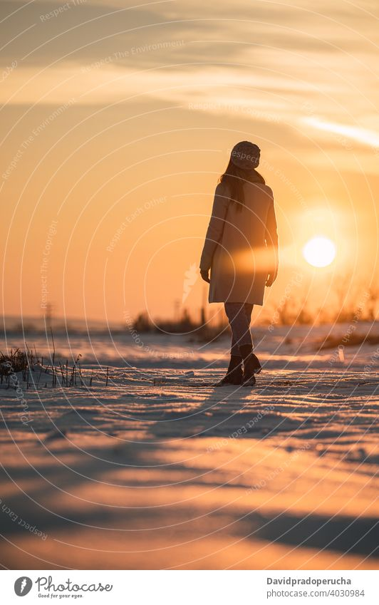 Woman enjoying sunset in snowy field winter countryside nature alone season fresh cold sundown recreation lifestyle weather wintertime harmony calm scenic
