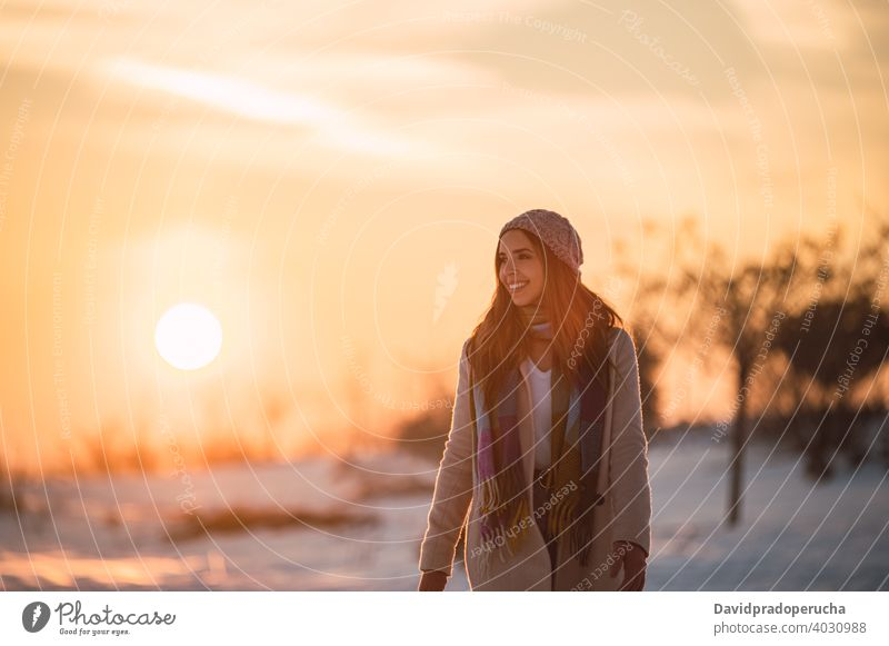 Woman walking on snowy field at sunset winter countryside happy nature season enjoy glad fresh cold cheerful stroll smile sundown recreation lifestyle weather
