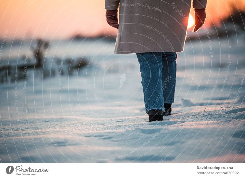 Anonymous person walking on snowy field winter leg boot footprint sunset alone nature season sole fresh countryside cold weather wintertime evening stroll