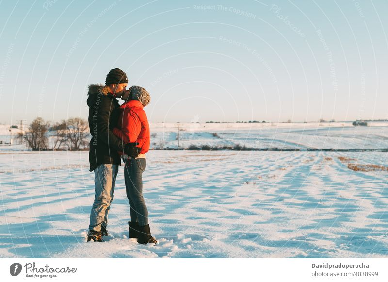 Couple kissing in snowy field couple winter countryside love romantic together relationship hug affection fondness embrace amorous tender bonding cuddle in love