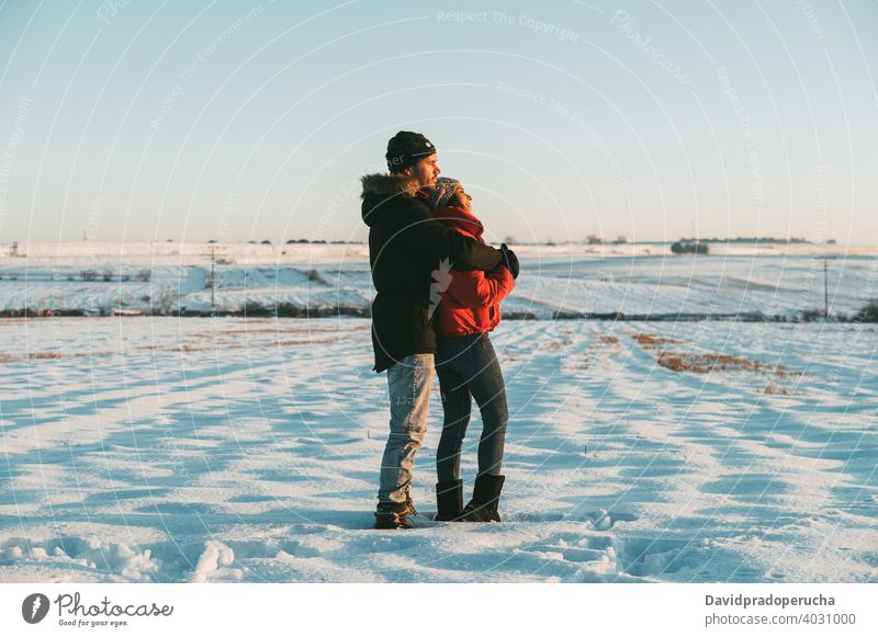 Couple hugging in snowy field couple kiss winter countryside love romantic together relationship affection fondness embrace amorous tender bonding cuddle