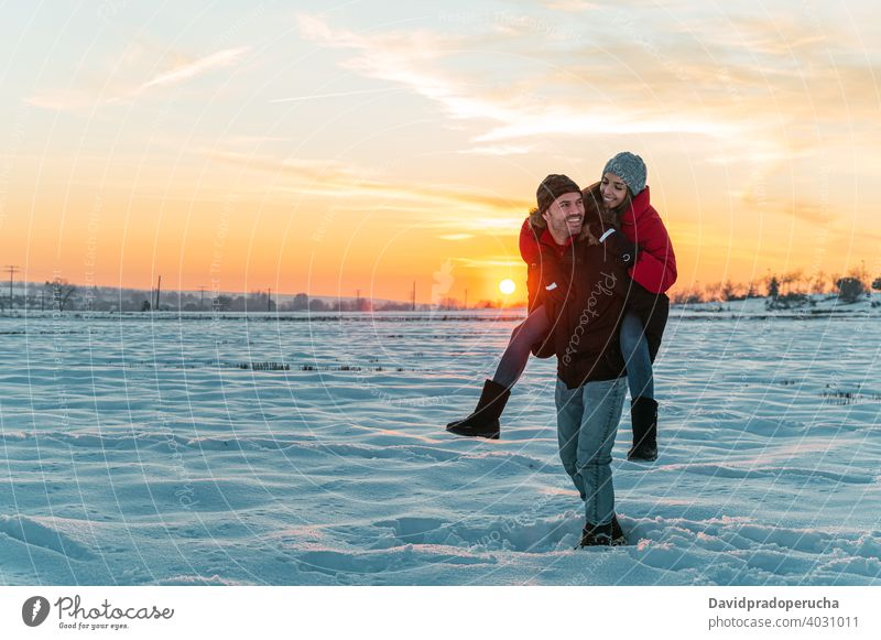 Happy couple having fun in snowy field piggyback winter cheerful countryside love together ride joy laugh romantic relationship affection excited fondness