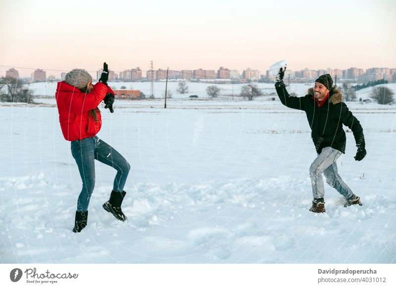 Cheerful couple playing snowballs in winter field having fun cheerful enjoy together countryside love romantic relationship affection fondness girlfriend