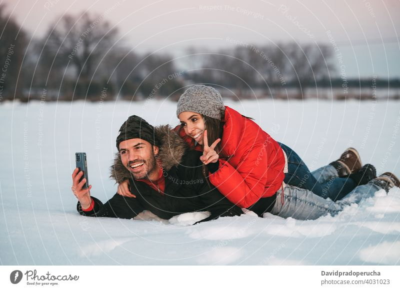 Laughing couple taking selfie on snow winter having fun cheerful countryside love together smartphone joy laugh field romantic relationship affection excited