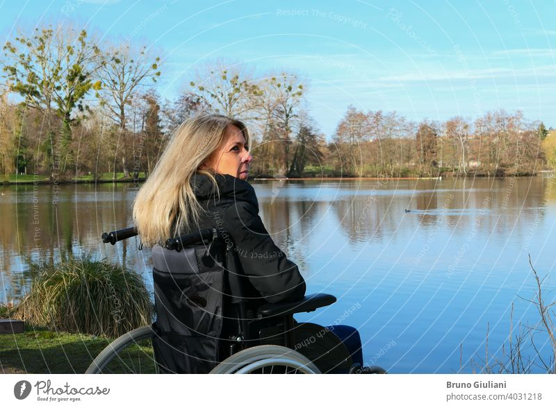 Concept of disabled person. A woman in a wheelchair outside in the nature in front of a lake. adult beautiful blonde hair caucasian concept contemplation