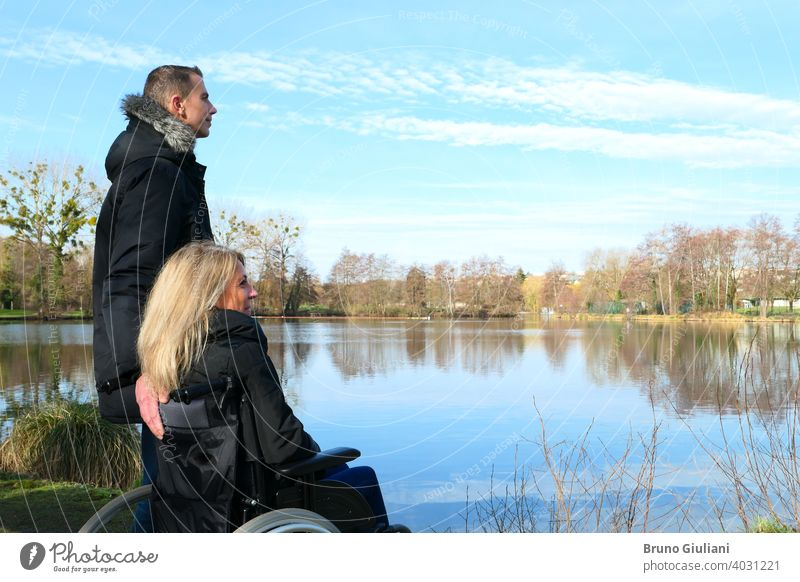 Concept of disabled person. A woman in a wheelchair with a man standing next to her, outside in the nature in front of a lake adult concept contemplation couple