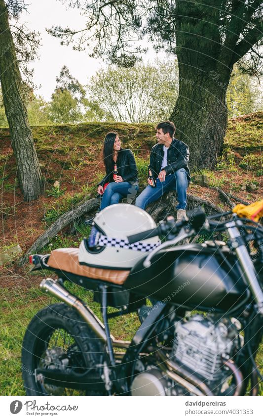 Couple resting from a motorcycle trip attractive couple smiling enjoying vintage alcohol-free beer landscape drinking talking custom built trees retro bike