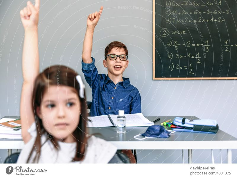 Students with mask on table raising hands at school boy talking asking coronavirus student class participating safety new normal people girl epidemic education