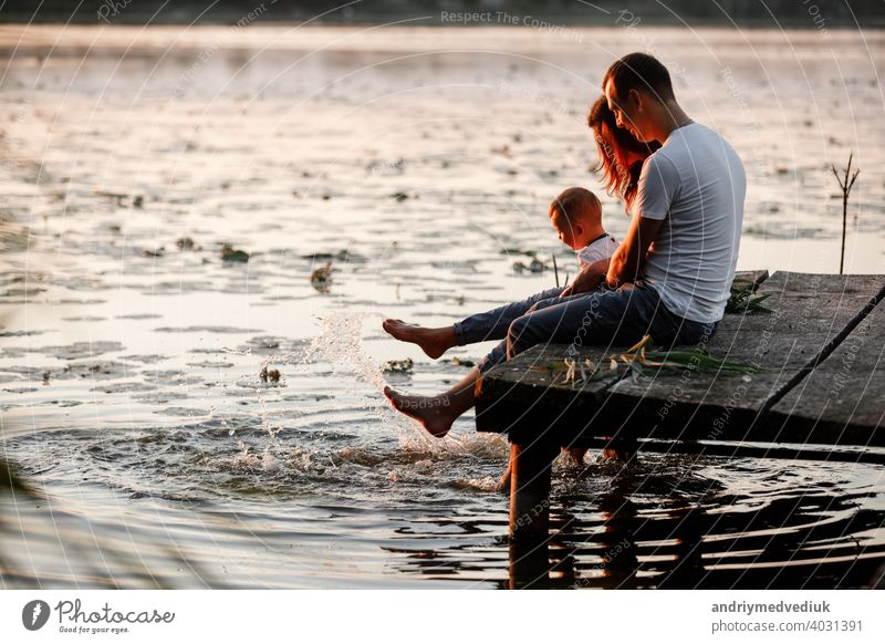 Young parents and their little son sitting on the wooden pier near the lake, at sunset on summer day. family mother young autumn father fall portrait bridge