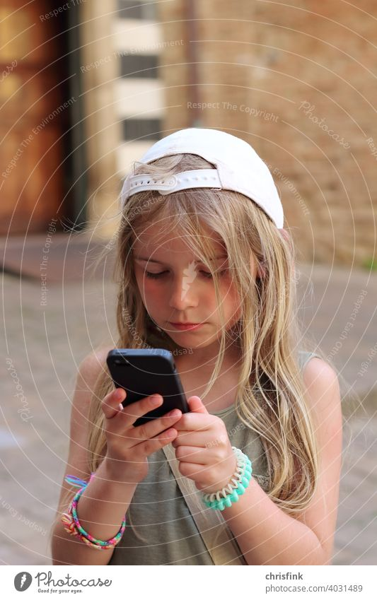 Girl in cap looks at mobile phone Child teen youthful Media Consumption peril media society Addiction Cellphone Electronics Internet Mobility Chat social media