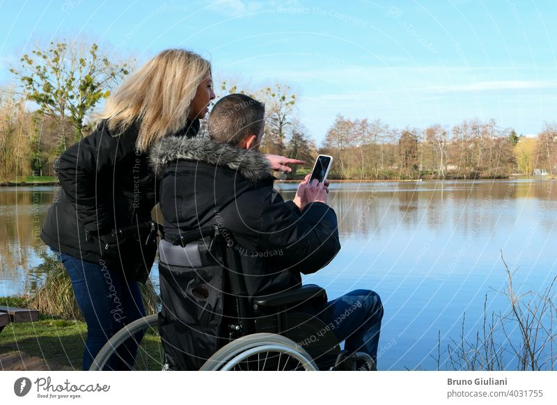 Concept of a person with a physical disability. A man in a wheelchair with a woman standing beside him. Couple using technology while looking at a smartphone. Rural scene by a lake.