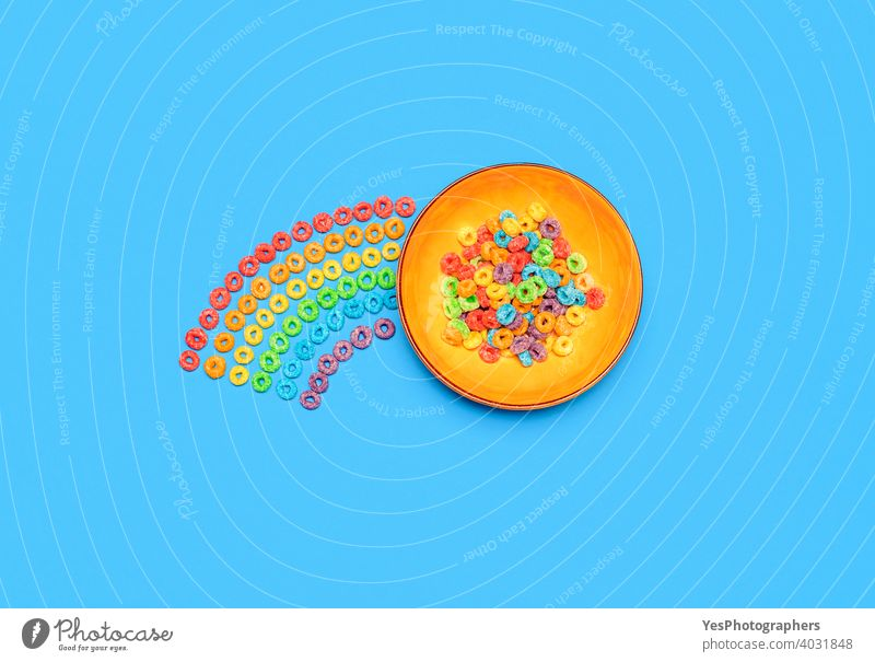 Cereal bowl isolated on blue background. Rainbow fruit-flavored ring cereals, top view above view assorted breakfast cereal bowl cheerful childhood childish