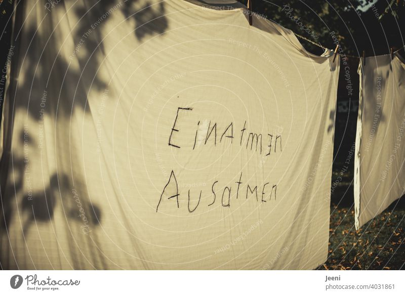 """""""EINATMEN AUSATMEN"""" on a bed sheet on a clothesline with shadows cast by a tree in low sun 