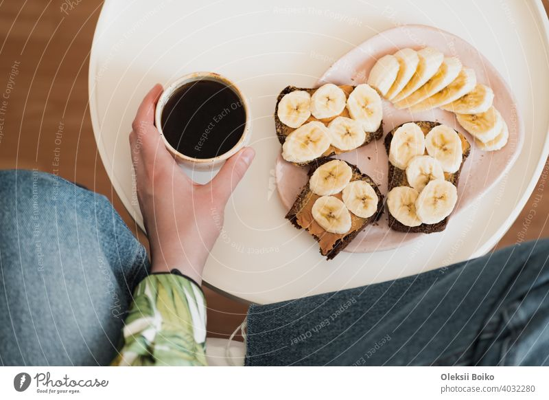 Woman holds a cup of black coffee, shot directly above. Having healthy fruit and peanut butter sandwich for breakfast, drinking morning coffee at home banana