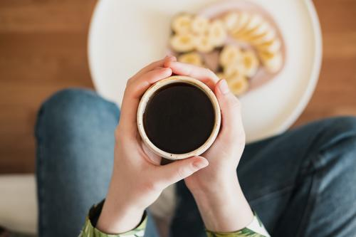 Woman holding a cup of black coffee, shot directly from above. At breakfast, drinking morning coffee at home Parts of body Breakfast Close-up Coffee Cup