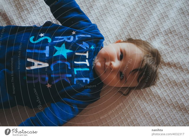 Little baby in blue lying down on a bed babyhood cute lovely girl bedroom home family adorable pajama playful face pretty brown hair blue eyes comfort lazy cozy