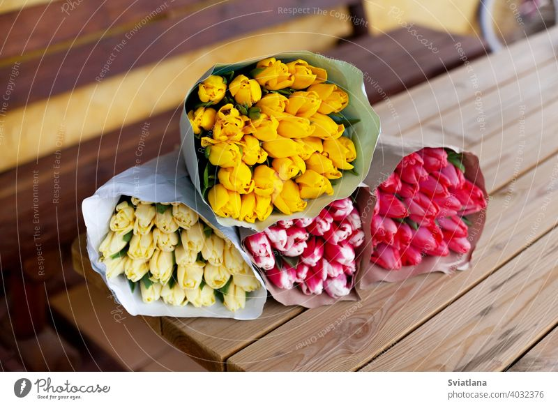 Several bouquets of tulips of different colors in paper packaging lie on a wooden table. Women's Day, Mother's Day, Valentine's Day. A gift, greeting card, place for text
