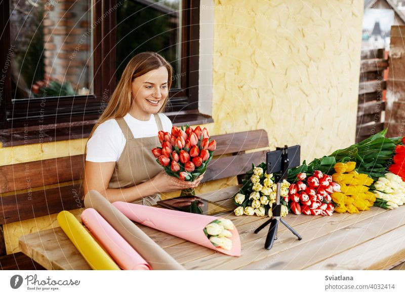 A young female florist packs bouquets of tulips in her shop and shoots a video master class for her blog. Women's Day and Valentine's Day woman phone mobile