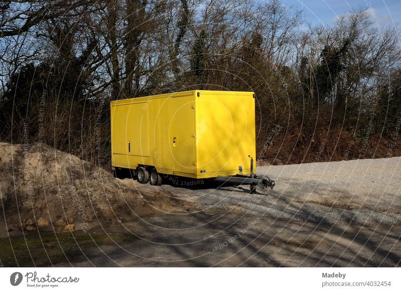 Tandem trailer with bright yellow body on a lonely gravel parking lot in Lemgo in Ostwestfalen-Lippe, Germany Trailer sales booth Yellow Snack bar Market stall