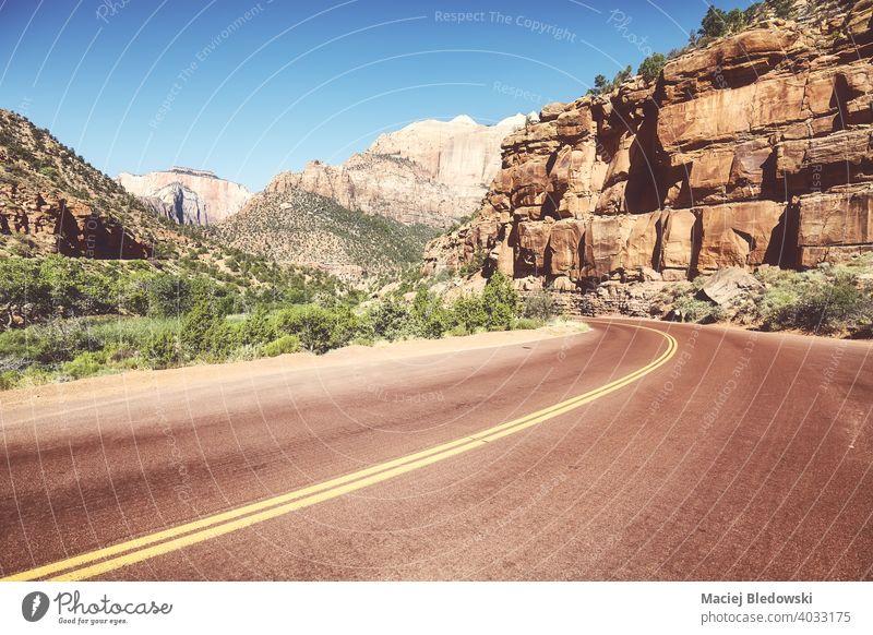 Asphalt road in Zion National Park, retro color toning applied, Utah, US. asphalt highway empty valley travel trip nature park scenery mountain wanderlust