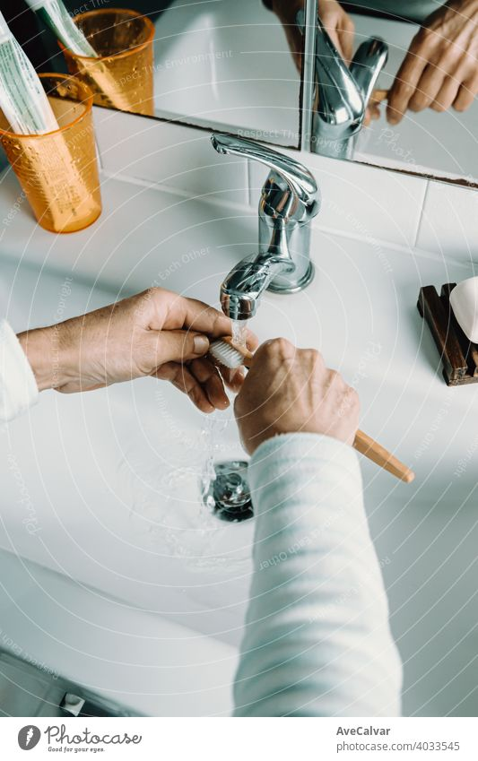 Old woman washes bamboo toothbrush with water and washes her teeth health care mouth bathroom female white age dental elderly mature senior person smile aged