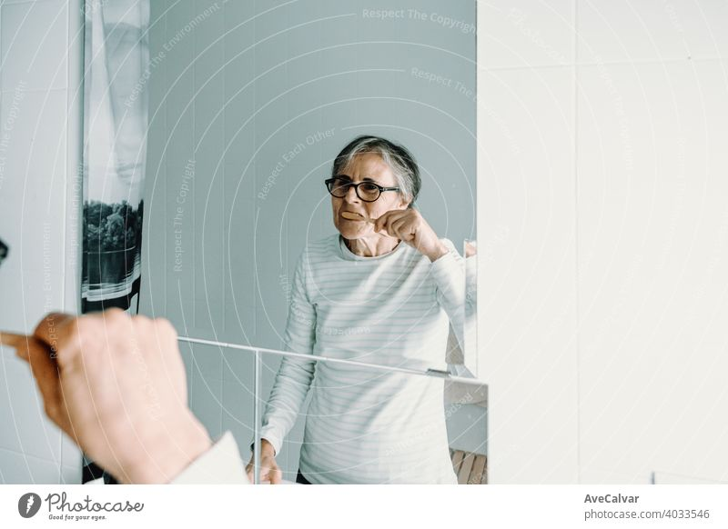 Old woman washes her teeth in front of a mirror with a bamboo toothbrush health care mouth bathroom female white age dental elderly mature senior person smile