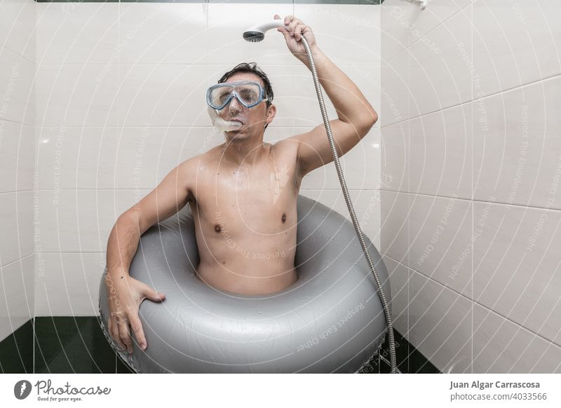 Man with swimming gear enjoying shower water man bathroom quarantine home concept adult imagine beach male snorkel goggles ring pretend wet shirtless rest relax