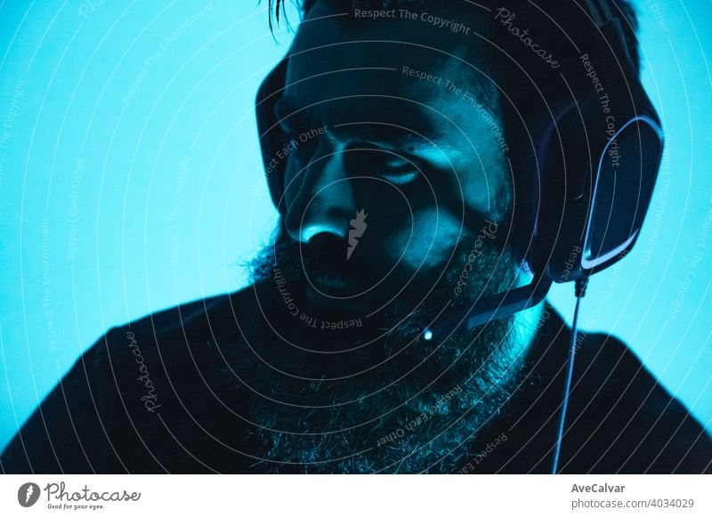 A young man with beard holding a gaming headset on serious face game male person computer entertainment guy online player internet fun technology keyboard