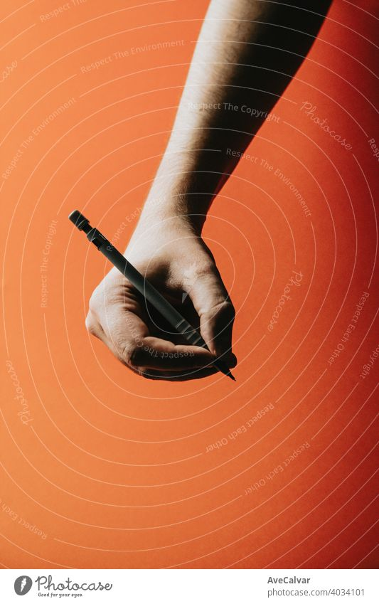 A young hand grabbing a mechanical pencil over a orange background with deep shadows office design paper education drawing business tool school isolated write