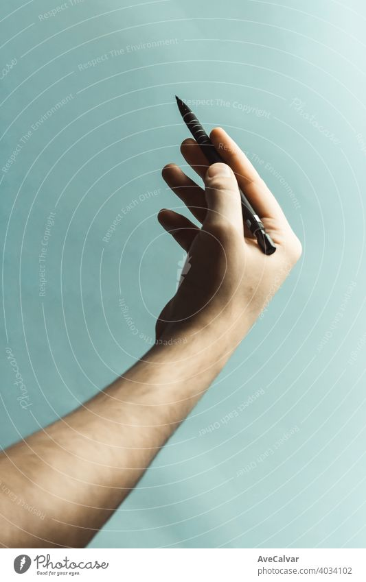 A young hand grabbing a mechanical pencil over a pastel blue background with deep shadows office design paper education drawing business tool school isolated