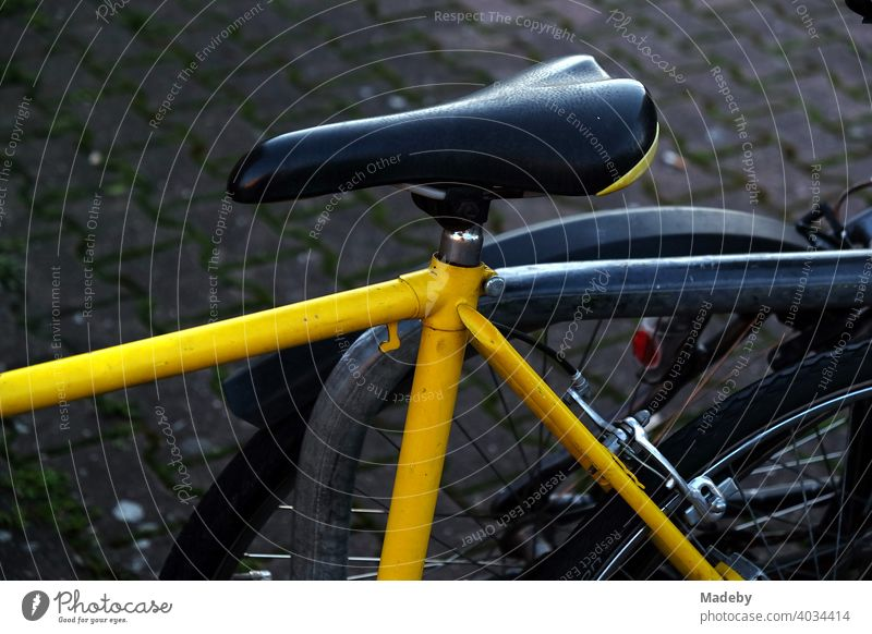Racing bike with yellow frame and narrow saddle in the evening at the Hanauer Landstraße in the Ostend of Frankfurt am Main in Hesse Bicycle Wheel Racing cycle