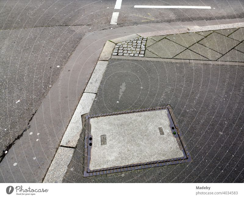 Street corner with curb, asphalt and various grey paving stones in Frankfurt am Main in Hesse cross Gully manhole cover Drainage system Gray Shades of grey off