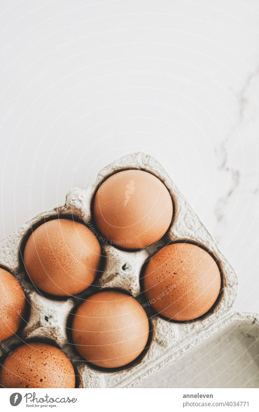 organic eggs in egg box on white marble kitchen table authentic breakfast brown cardboard carton chicken cinematic closeup container copyspace easter eat