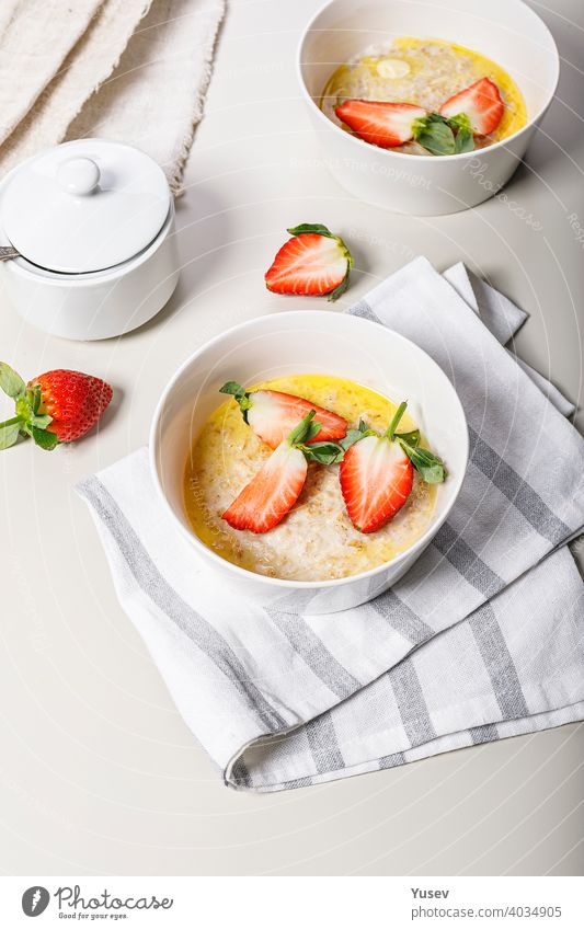 Classic oatmeal with butter and fresh fruit. Sweet strawberries. Delicious and healthy breakfast. Food still life on a light background. Ideas and recipes for home meals. Vertical shot