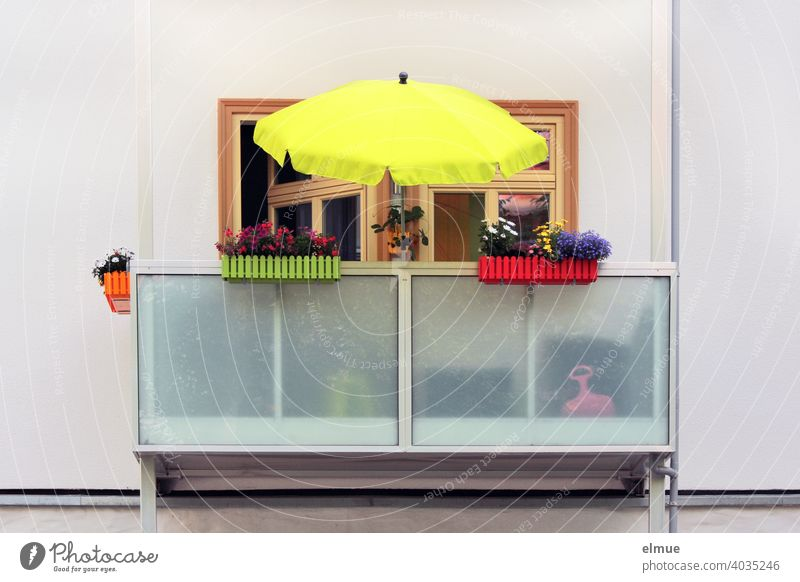 Balcony with yellow parasol and different colored plastic flower boxes in which flowers bloom / color / vacation on balcony Sunshade dwell balcony boxes