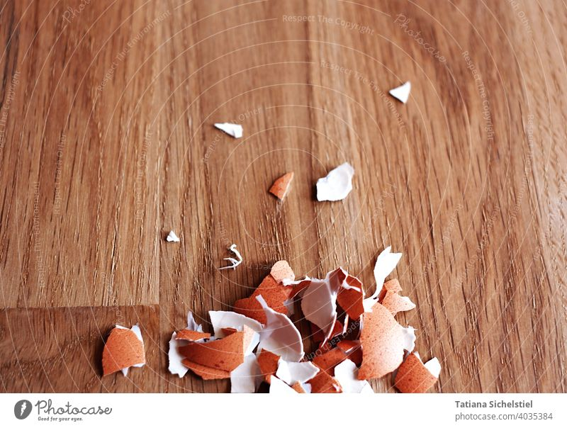 Peeled eggshell fragments lie on a wooden table at the lower edge of the picture Eggshell peel Brown Wood Eating Breakfast Easter Protein naturally Close-up