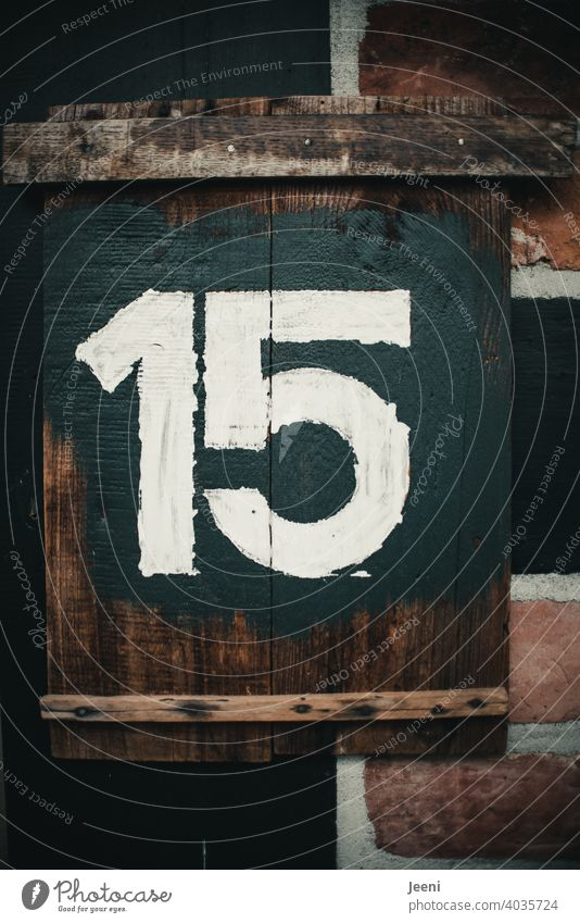 House number fifteen written as number 15 on rustic wooden board with white paint on dark background Digits and numbers digit Numbers and numbers