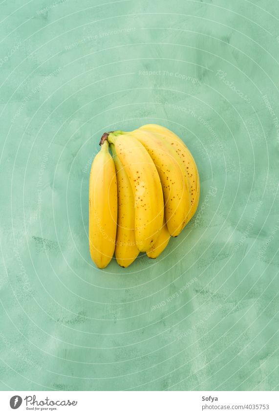 Whole bunch of bananas fruit on green yellow background ripe fresh summer organic texture close group stem sweet delicious food healthy whole exotic natural
