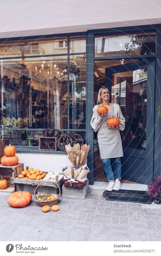 Smiling woman is holding pumpkins in front of her shop happy smile florist flowers concept backgrounds healthy store girl apron orange urban outdoors lifestyle