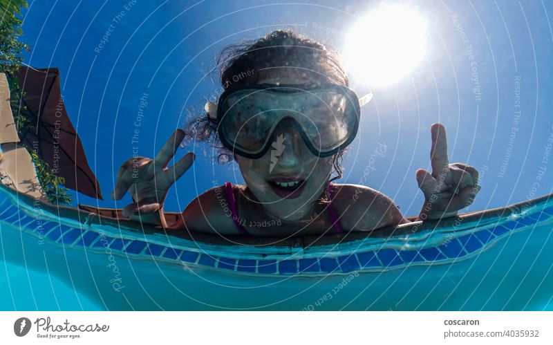 Little girl on a poolside. View from below. active bikini blue bubbles child childhood diving enjoy face fun funny goggles happiness healthy kid kids learn