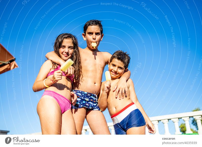 Three funny kids eating an ice lolly boy brother caucasian cheerful child childhood children cream daughter day dungaree enjoy exterior family food fresh frozen