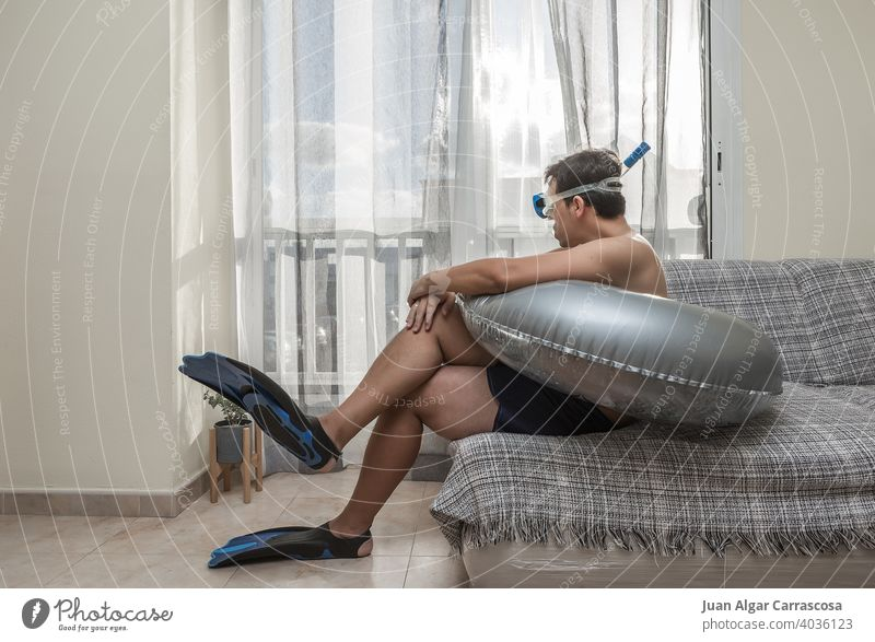 Male swimmer looking out window in living room man beach sit admire sofa quarantine home concept male adult imagine couch pretend gear snorkel goggles flipper
