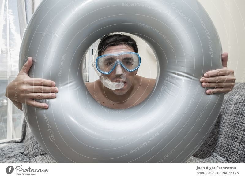 Man looking at camera through swimming ring man beach play pretend quarantine home concept adult living room male imagine gear snorkel goggles dream equipment