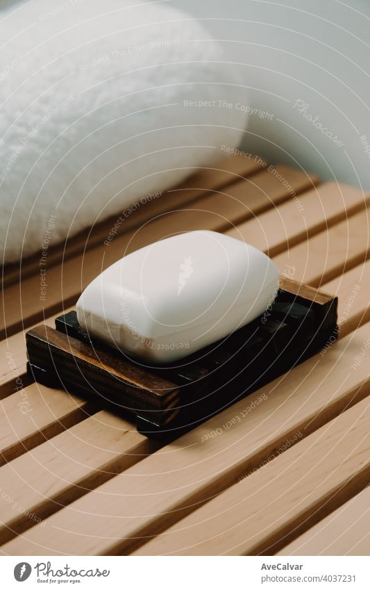 A hard soap over a wooden soap dish in a bathroom with a spa concept relax shower clean wash background white hygiene closeup texture health care water beauty