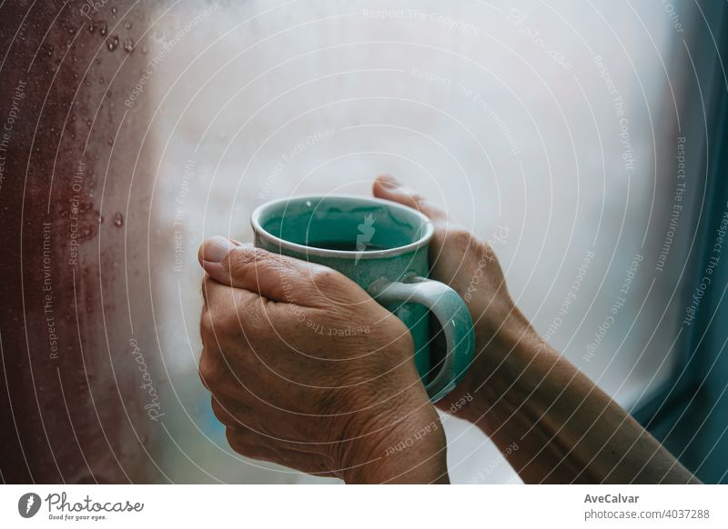Two old hands grabbing a fast tea during a cold dayTwo old hands grabbing a fast tea during a cold day drink cup water hot woman kitchen background person pour