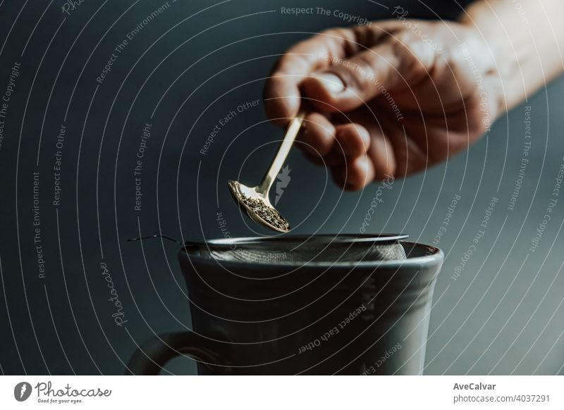 A old hand preparing a tea over a dark background with copy space and dark tones drink cup water hot woman kitchen person pour kettle beverage green female