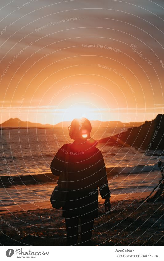 A traveler in front of a colorful sunset in the beach wearing a face mask, wellness concept, life and freedom woman happy silhouette people inspiration summer