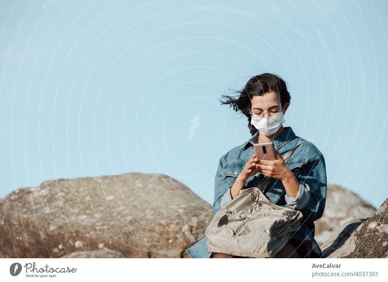 A young woman wearing a mask checking his phone while the wind blows with copy space female mobile people nature person smiling happy beautiful cellphone