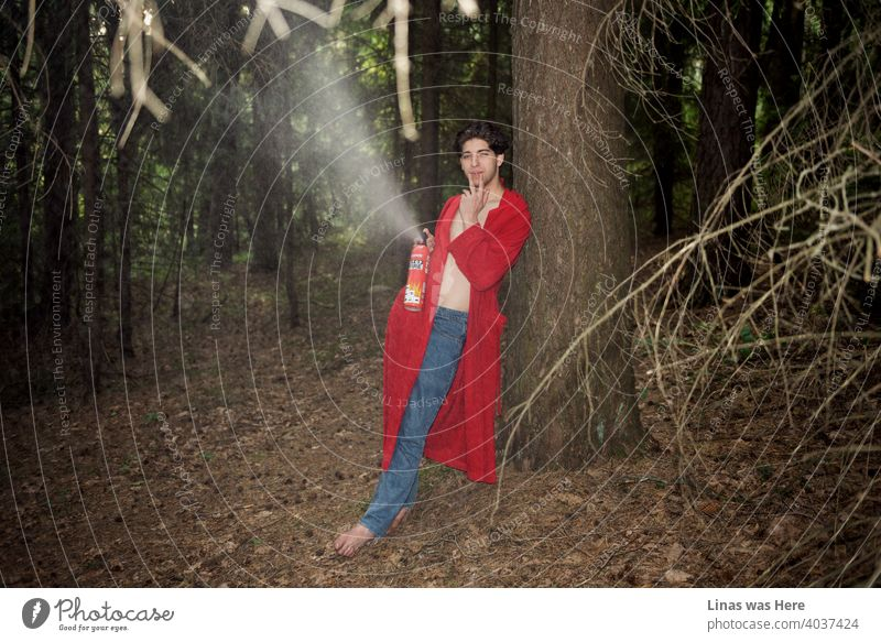 A wild man in the forest is taking down an imaginative fire with a fire extinguisher. Dressed in blue jeans and a red bathrobe he is having fun in these woods. Smoking a cigarette and just enjoying nature.